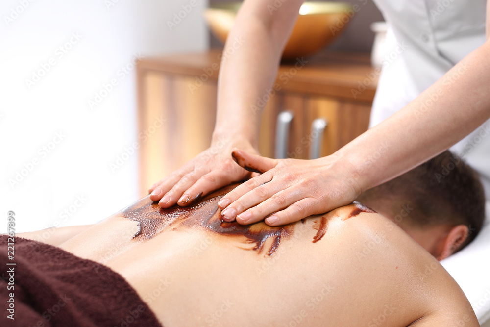Fototapeta Masaż czekoladowy pleców. Mężczyzna na zabiegu masażu w salonie odnowy biologicznej.