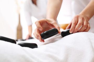 Randka w spa, masaż kamieniami dla niej i dla niego. Kobieta i mężczyzna razem na masażu w gabinecie spa.