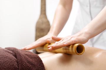 Masaż bambusowy. Masażysta masuje ciało przy użyciu bambusowych kijów.