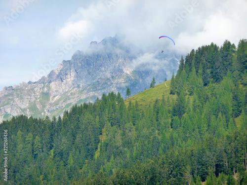 Paragleiten Ein Paragleiter schwebt über den Wipfeln eines Tannenwaldes.