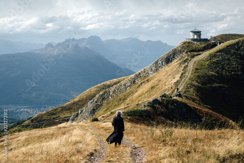 Fototapeta Orthodox priest walking toward mountain chapel