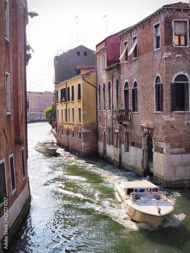 Foto op Plexiglas Venetie The canal is surrounded by ancient buildings, gondolas and boats in Venice