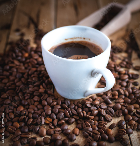 Deurstickers koffiebar Close-up of black coffee in white cup, with coffee beans on wooden background