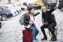 Due Amiche In Viaggio Si Siedono Sopra Le Valige E Indicano Qualcosa