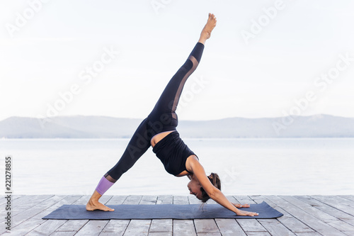 Poster Ecole de Yoga Young attractive smiling woman practicing yoga on a lake