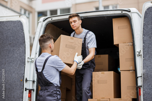 Canvastavla  Two young handsome movers wearing uniforms are unloading the van