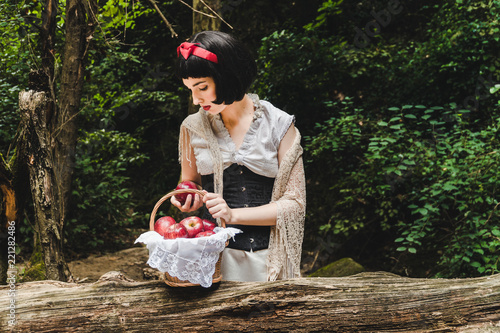 Fototapeta  Snow White is in the forest, holding and looking to a red apple next to a basket full of apples