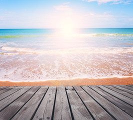 Fototapeta Morze Sandy beach on bright sunny morning with wooden walkway. Tropical resort