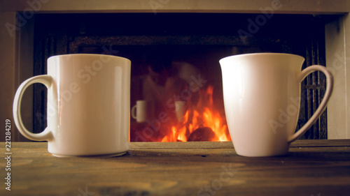 Closeup image of two mugs of hot tea on wooden desk against burning fireplace at Wallpaper Mural