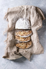 Sliced Christmas Cake, Traditional German Festive Baking. Wholegrain Stollen With Raisins And Sugar Powder On Linen Napkin Over Gray Texture Background. Top View, Space