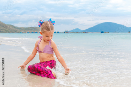 Valokuva  Little beautiful girl dressed in swimsuit as a mermaid sits on the seashore