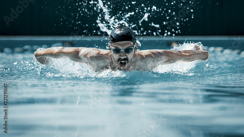 Cuadros en Lienzo The dynamic and fit swimmer in cap breathing performing the butterfly stroke at pool