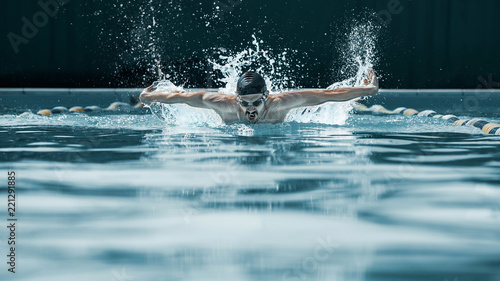 Fototapeta The dynamic and fit swimmer in cap breathing performing the butterfly stroke at pool. The young man. The fitsport, swimmer, pool, healthy, lifestyle, competition, training, athlete, energy concept obraz