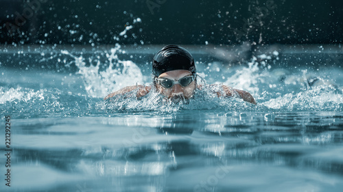 Fototapeta The dynamic and fit swimmer in cap breathing performing the butterfly stroke at pool