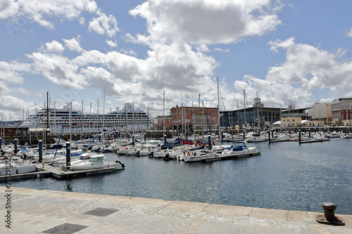 The piers of La Coruña marina sea port with many sailing boats and a blue sky with some clouds