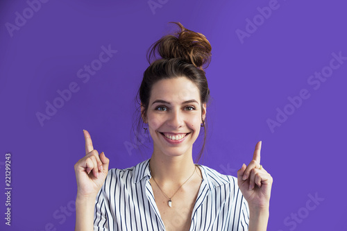 Photo A calm, cute young woman points her fingers at something above her head to something important, something to look out for