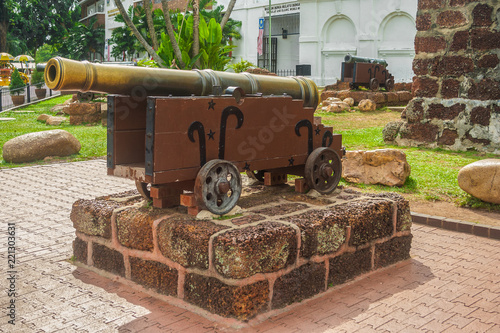 An old large Portuguese bronze cannon on a red sandstone platform at A Famosa, a former Portuguese fortress located in Malacca, Malaysia Wallpaper Mural