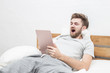 Caucasian young man holding tablet and yawning want to sleep feeling so tried on bed in bedroom