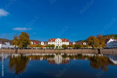 Fotomural Beautiful panoramic view of a row of baroque houses and the Huguenot Museum in the middle, mirrored on the water surface of the harbour basin on a nice autumn day in Bad Karlshafen, Germany