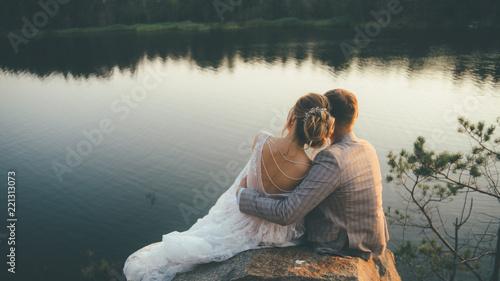 Fotografia  beautiful wedding couple sitting hugging looking to the sunset