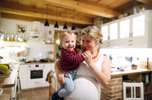 Beautiful Pregnant Woman Carrying A Toddler Boy In The Kitchen At Home.