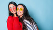 canvas print picture Like a sisters! Two beautiful young girl friends in sunglasses posing with smile and have a fun on blue background