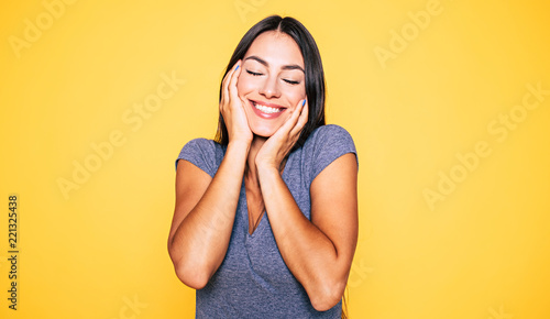 Obraz na plátně Young attractive cute brunette woman in gray T-shirt is posing and looking on ca