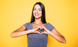 canvas print picture Love, heart shape, peace. Sign, gesture or symbols. Portrait of cute attractive smiling brunette woman, girl shows heart sign with help of her hands on yellow background in casual wear