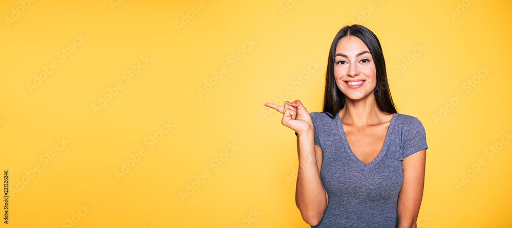 Fototapeta Photo of young excited beautiful happy brunette woman, girl pointing away and smile isolated on yellow background banner