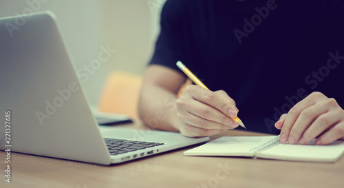 close up student man hand using pencil for doing text exam after finish course online learning , self study education concept