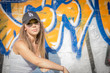 Portrait of young beautiful woman wearing white tank shirt and blue jeans and black hat on brick wall with graffiti background