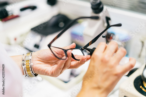Pinturas sobre lienzo  Female optician measuring and preparing glasses on the latest digital device in optical store