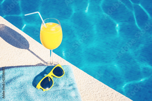 Attributes of summer vacation - sunglasses and a glass of juice - on the backgro Canvas Print