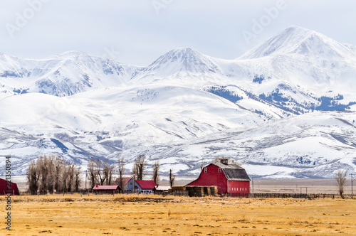 Montana Farm Below Massive Snow Covered Mountains Fototapeta