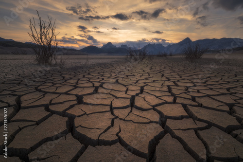 Earth cracked by extreme drought below a dramatic sunset.