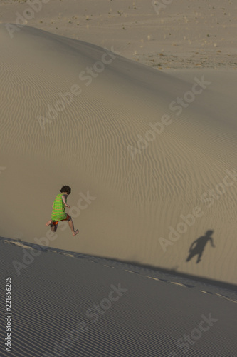 Boy jumping on sand dunes, Death Valley National Park, California, USA