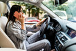 Portrait of woman driver talking her mobile phone while driving car.