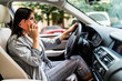 Young business Woman using her phone while driving the car