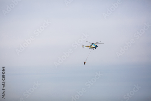 Tuinposter Helicopter Fire in forest. Helicopter dpirs and drops water in epicenter of incident