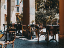Cozy Outdoor Cafe With Empty Wooden Tables Covered With A Tablecloth With Metal Flower Pots And Ashtries On It, Chairs Near; Exterior Of An Empty Street Bar On The Daytime Waiting For Its Visitors