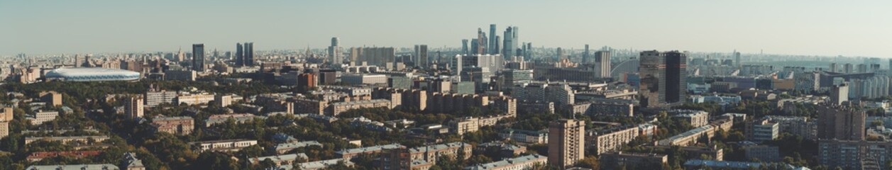 Fototapeta Panorama of evening summer cityscape with the residential district and dwelling houses in the foreground, multiple office skyscrapers and business high-rises in the distance; huge stadium on the left
