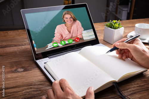 Fotografía  Person Writing On Notebook While Video Chatting