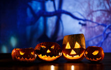 Orange Pumpkins With Scary Faces And Candles Lies On The Table In Front Of Dark Blue Background. Halloween Celebration Concept