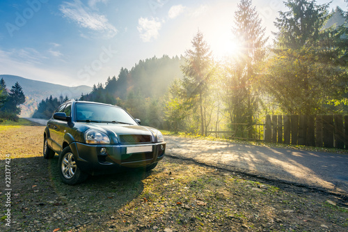 Obraz SUV on countryside road in foggy mountains. lovely transportation scenery at sunrise in autumn. travel by car concept - fototapety do salonu