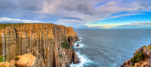 Photo The sun hitting the top of the cliffs at Cape Raoul