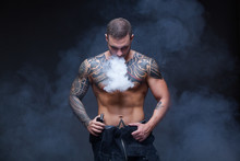 Vaper. The Man With A Muscular Naked Torso With Tattoos Smoke An Electronic Cigarette On The Dark Background