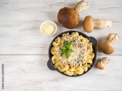 Pasta with penny bun on a cast iron pan on a white wooden table Wallpaper Mural