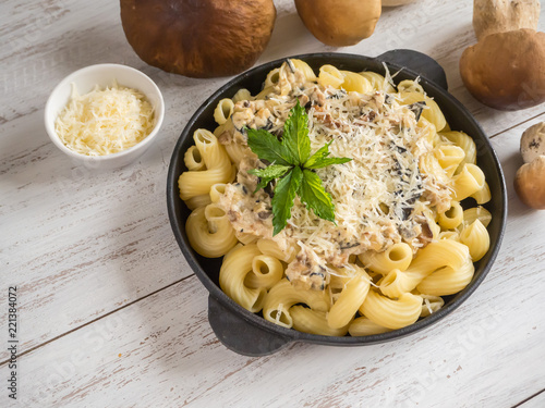 Photo Pasta with penny bun on a cast iron pan on a white wooden table