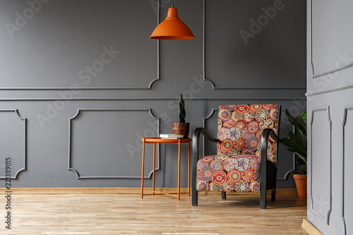 Bright orange ceiling light above a boho style armchair in ...