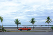 tropical beach with palm trees and a car in Cienfuegos, CUBA